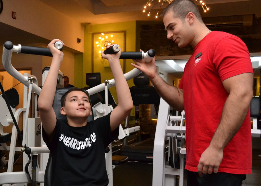 boy using weights machine with instructor