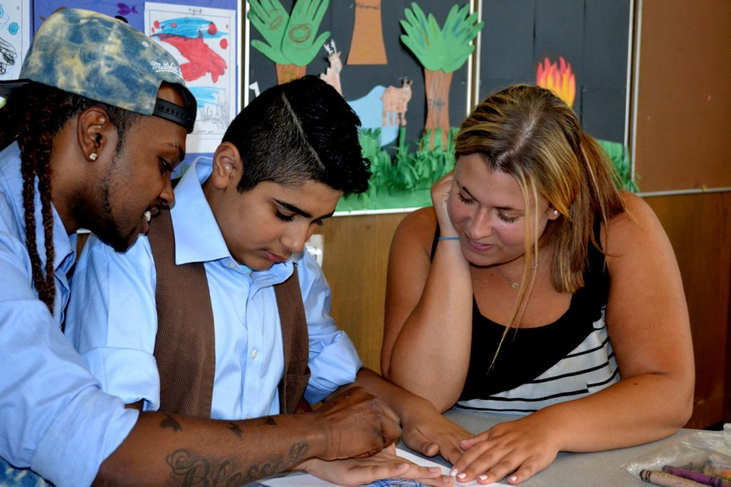 male student reading with two teachers